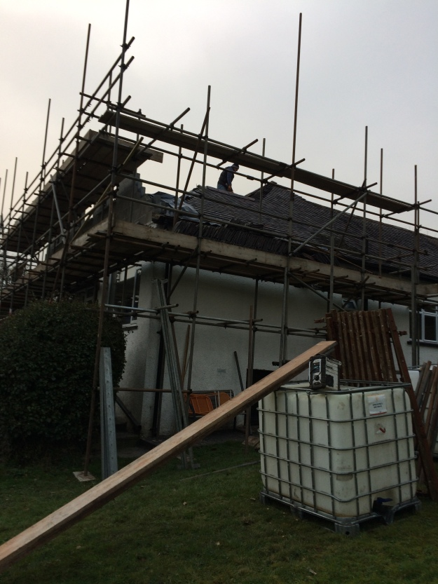 builder-cutting-away-roof-ready-for-beam-to-go-into-house