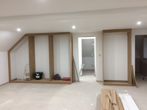 New large fitted wardrobes under construction on both sides of the doorway