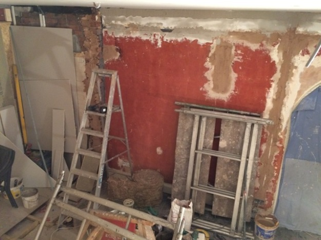 Wallpaper stripped off, walls plastered, ready for another coat, old red paint showing from a previous owner of Springdale