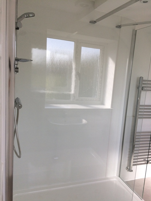 View of shower, reflection of window in showerboard